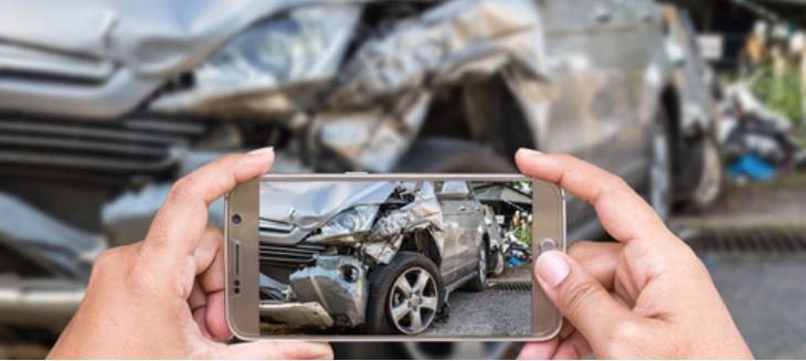 taking photo on cell phone of damaged vehicle